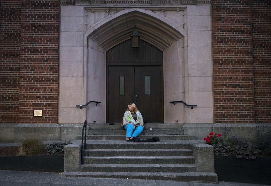 Milee Ballweg, 20, sits on the steps of a University District church where she sleeps just after 5:00 a.m. on Wednesday, July 11, 2018, in Seattle.