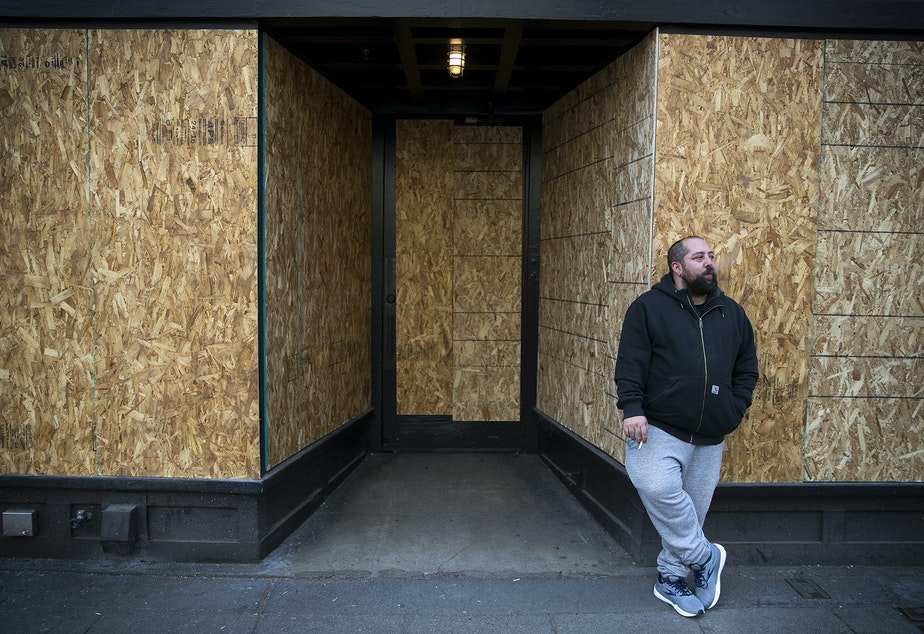 "caption: Andy Aronis, Assistant General Manager of King's Hardware, smokes a cigarette outside of the boarded up bar and restaurant on Tuesday, March 17, 2020, on Ballard Avenue Northwest in Seattle. ""I always felt good working in the bar industry because it's recession proof,"" said Aronis, who planned to file for unemployment. ""The only thing you don't consider working in this industry is if there is a medical pandemic and then we are in the worst industry you could be in."""