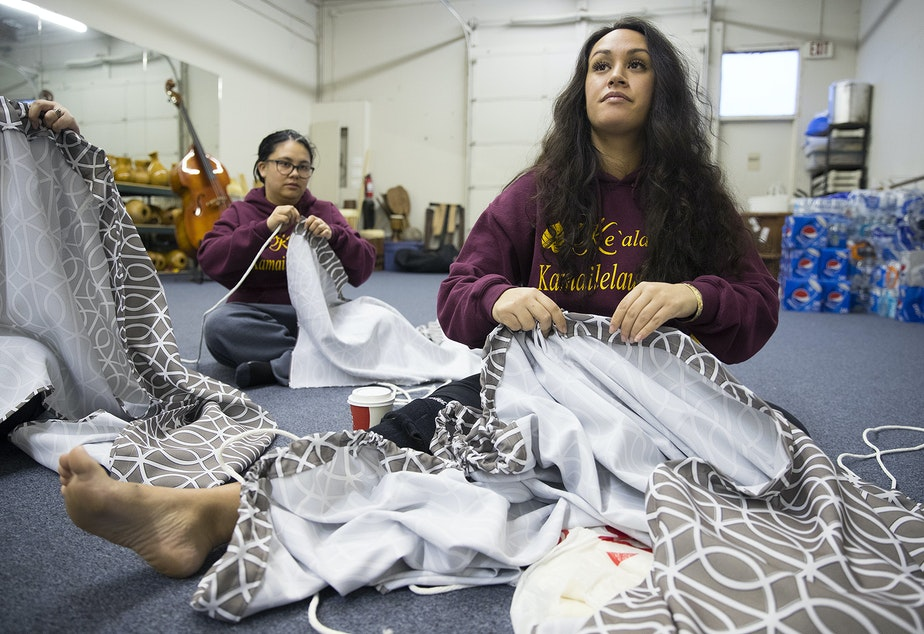 Leilani Kaaiwela-Pedreira, center, and Jessica Whalen, left, assemble their traditional Kahiko dresses on Thursday, March 22, 2018, at the halau in Federal Way.