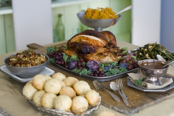 This Oct. 17, 2011 photo shows a sweet and spicy turkey surrounded by, clockwise from top, smashed harvest vegetables, oven-candied green beans amandine, gravy, brown sugar and oatmeal rolls and candied bacon stuffing in Concord, N.H.  (AP Photo/Matthew Mead)