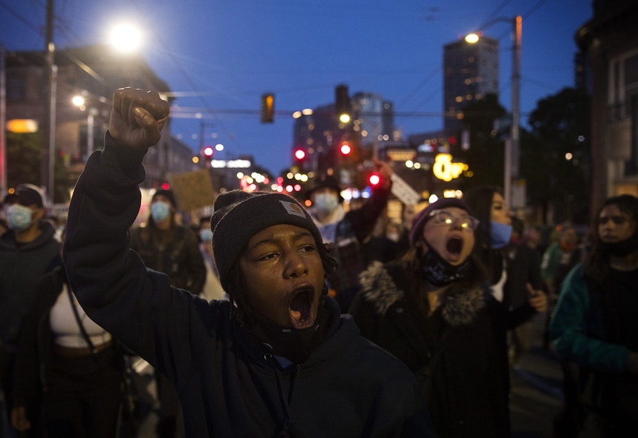caption: Tealshawn Turner leads a group of people protesting police brutality and violence against Black Americans back to the Capitol Hill Occupied Protest zone after marching to the Seattle Police Department's West Precinct building on the 19th day of protests in Seattle following the violent police killing of George Floyd, on Tuesday, June 16, 2020.