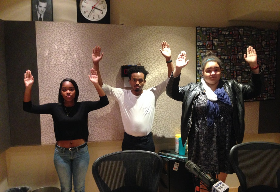 "caption: Yaninna Sharpley-Travis (left), Marcel Purnell and Devan Rogers. They are making the ""don't shoot"" pose, which has become a popular form of social media protest after the events in Ferguson."