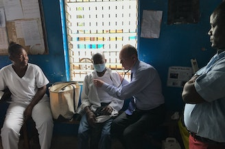 Dr. Paul Farmer examines a tuberculosis patient in Monrovia, Liberia.