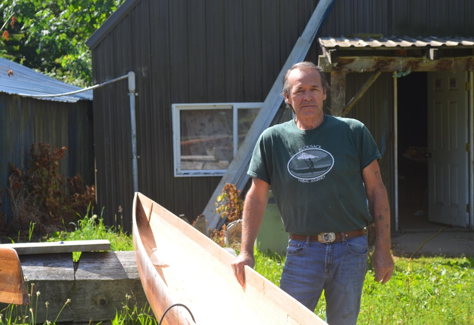 caption: George Swanaset Sr. with one of the racing canoes he crafts in Everson, Washington.