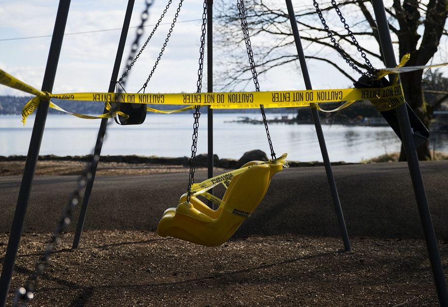 caption: A swing set is off limits and surrounded by caution tape as a result of the coronavirus outbreak on Wednesday, March 25, 2020, at Seward Park in Seattle.
