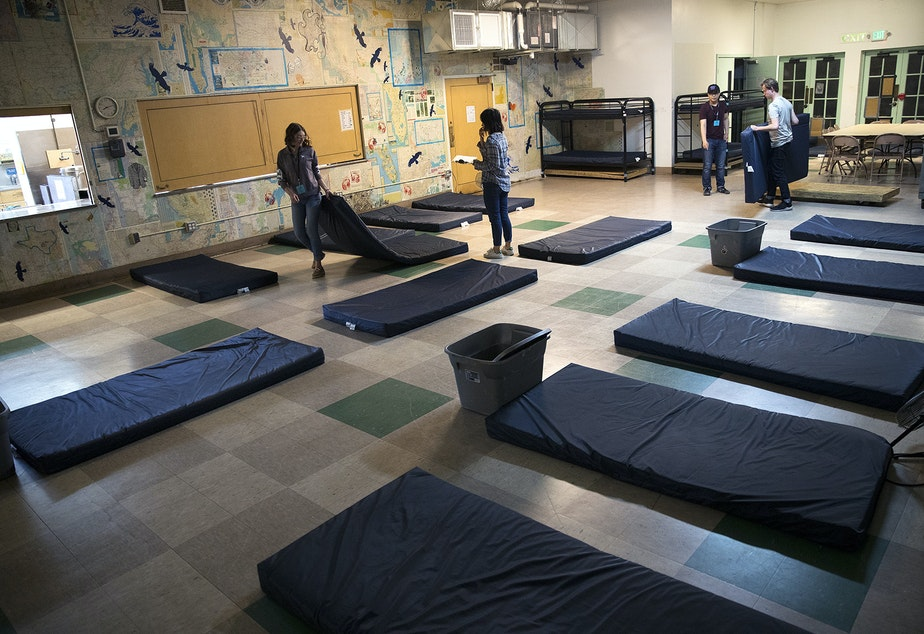 caption: Volunteers set up sleeping mats at ROOTS Young Adult Shelter on Tuesday, July 10, 2018, in Seattle. The shelter can accommodate up to 45 young adults a night.