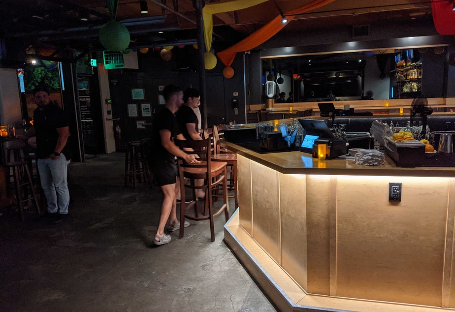 caption: Staff at Union Bar in Seattle put chairs back at the bar after Washington state officially reopened at 12:01 a.m. on June 30, 2021.