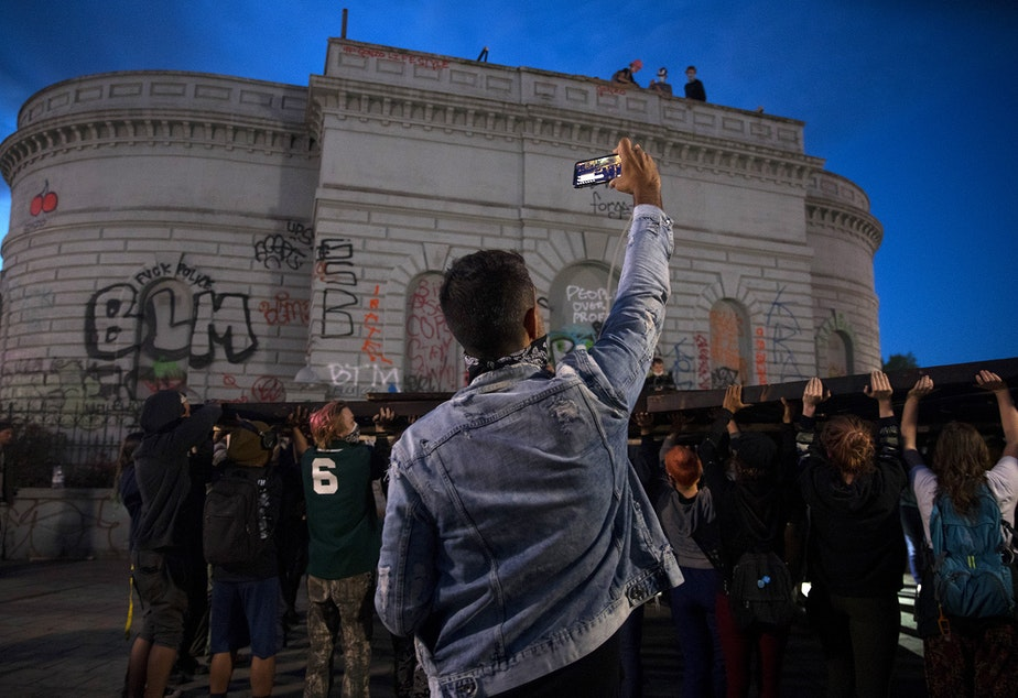 caption: A protester live-streams as others attempt to lift a Black Power fist art instillation inside the Capitol Hill Occupied Protest Zone on Tuesday, June 16, 2020, in Seattle. As a result of safety concerns, it was decided that the structure would be raised the following day instead.