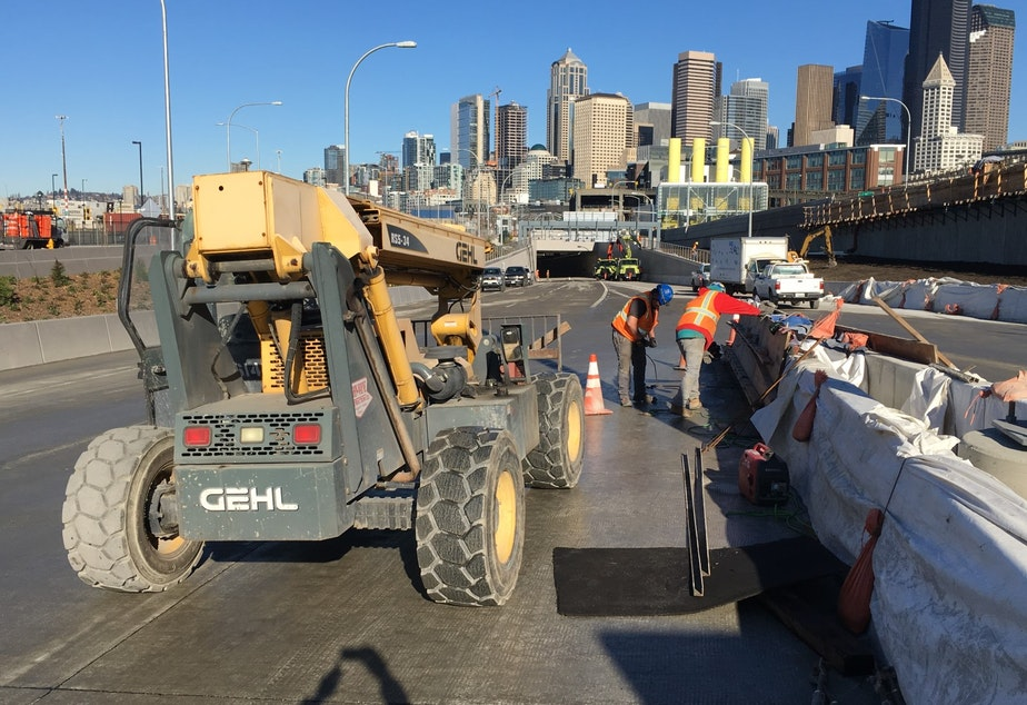 caption: Workers remove forms from curing concrete barriers, one of the final steps in the days before Seattle's new waterfront tunnel opens.
