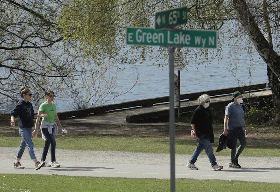 caption: Some people wearing masks, and some not, walk on a pathway at Green Lake Park, Friday, April 10, 2020, in Seattle.