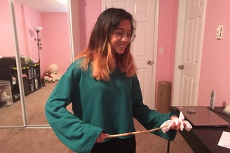 Arya Barlinge uses her homemade wand, crafted from an apple tree, to demonstrate how she would channel energy to the headband she holds.