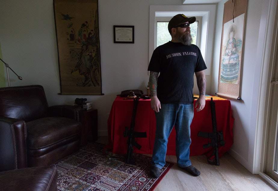 caption: Duke Aaron stands in front of his Buddhist alter and guns, in his Seattle home on February 15, 2020. Aaron said despite owning guns, he isn't voting on this one issue alone and places priority on health care issues.