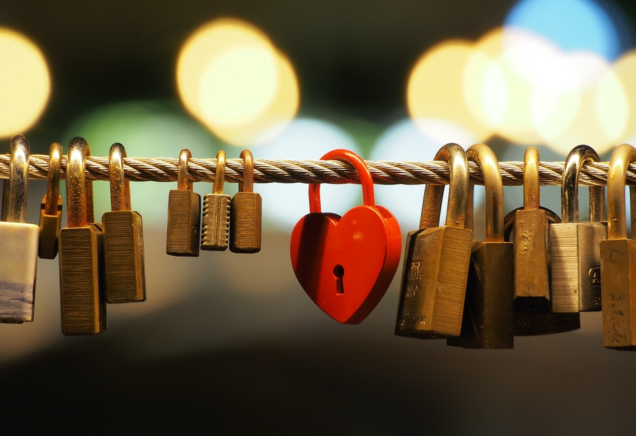 caption: a red heart shaped padlock amongst several other brass and copper ones on a rope
