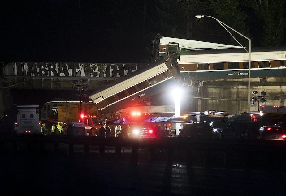 caption: The scene of an Amtrak derailment over Interstate 5 taken in the evening on Monday, December 18, 2017 from Mounts Road.