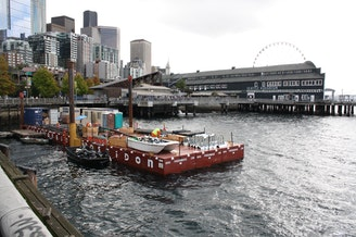 Utilities must be rerouted before Seattle's current seawall comes down. But with no room on the crowded sidewalk to stage construction materials, the job shack for utility workers resides on a barge.