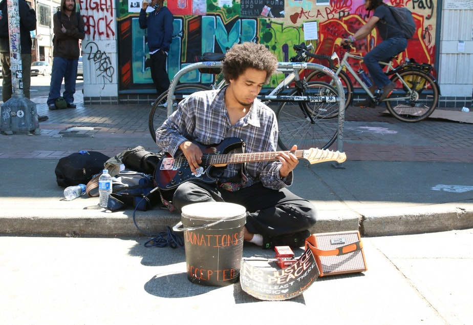 caption: Ahmahd Odom busks in the CHOP on Monday, June 22, 2020