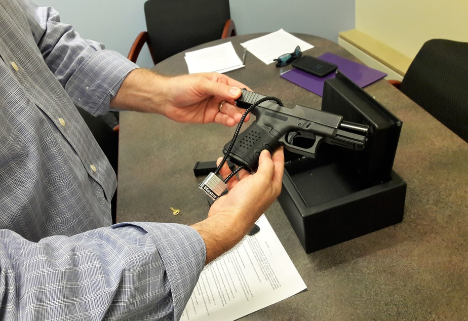 caption: Edmonds City Council President Mike Nelson demonstrates how he uses a safe for his pistol.