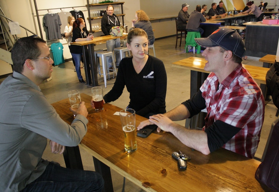 Blue Origin employees Devin Vezetinski (C) and Dan Cody (R) chat up Edward Matyasi (L), who just interviewed with the company. Blue Origin likes this brewery & taproom so much, it sent a postcard from Airways Brewing Company up in one of its rockets.