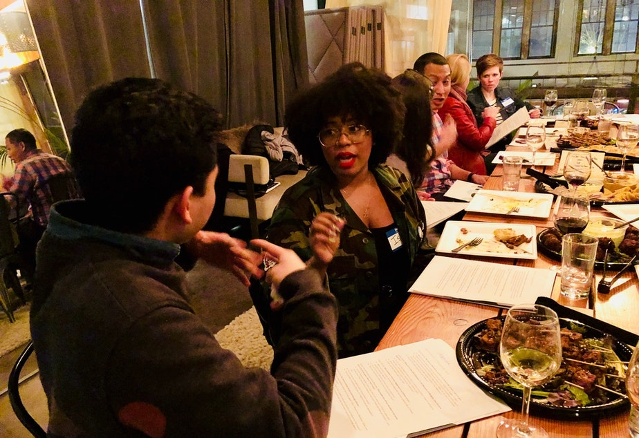 caption: Ishea Brown talks with Joe Santiago at KUOW's first Pop-Up Curiosity Club dinner at The Cloud Room in Seattle. February 28, 2019.