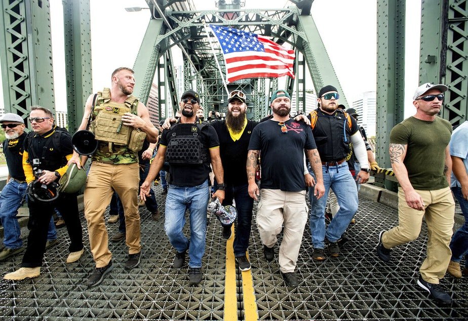 "caption: Members of the Proud Boys, including chairman Enrique Tarrio, and organizer Joe Biggs, third from right, march across the Hawthorne Bridge during an ""End Domestic Terrorism"" rally in Portland, Ore., on Saturday, Aug. 17, 2019. Biggs was arrested Jan. 20, 2021 for taking part in the siege of the U.S. Capitol on January 6, 2021."