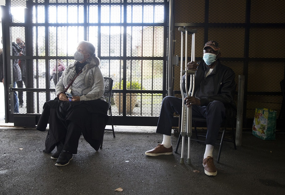 caption: Patricia Riales, left, and Ulysses Glenn, right, wait for 15 minutes after receiving the first dose of the Moderna Covid-19 vaccine on Wednesday, February 3, 2021, during a vaccine clinic set up by the Somali Health Board in partnership with the Othello Station Pharmacy to vaccinate 100 seniors in the community at the Brighton Apartments complex on Rainier Avenue South in Seattle.