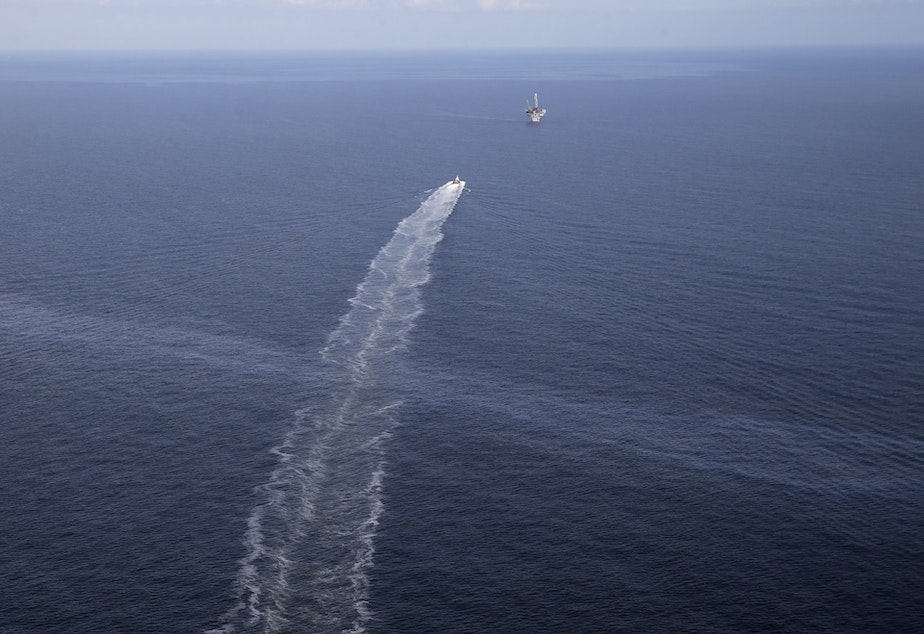 caption: The wake of a supply vessel heading toward a working platform crosses over an oil sheen drifting from the site of the former Taylor Energy oil rig in the Gulf of Mexico in 2015. The Coast Guard says it has contained the oil spill.