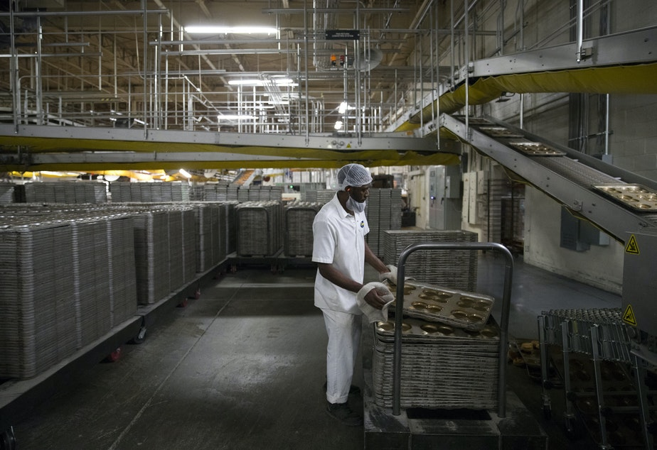 Guy Patrice stacks trays at 10:05 p.m. on Wednesday, June 12, 2019, at Franz Bakery on 6th Avenue in Seattle. In one 8-hour night shift, between 48,000 and 50,000 loaves of bread are made.