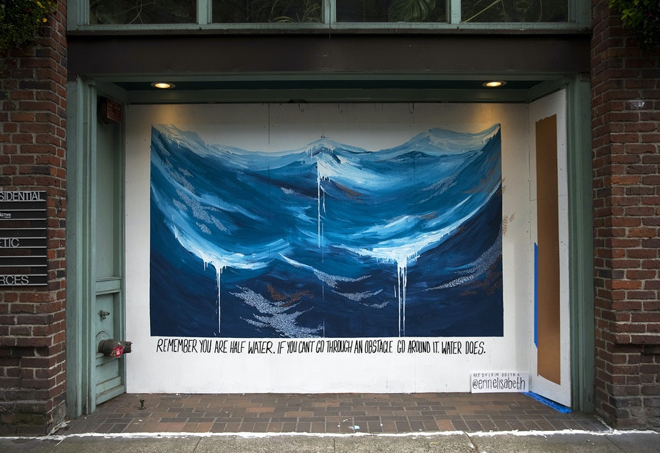 "caption: A mural painted by Erin Oostra is shown on Tuesday, April 28, 2020, along First Avenue South in Seattle. ""Remember you are half water. If you can't go through an obstacle, go around it. Water does,"" reads the mural."