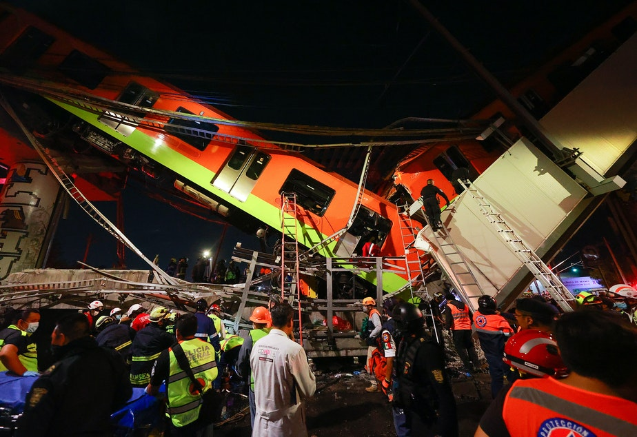 caption: Emergency personnel search for survivors after a raised subway track collapsed Monday night in Mexico City.