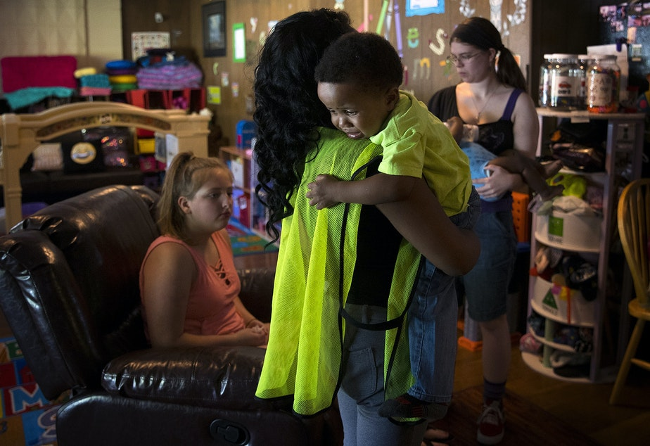 caption: Tiffany Montgomery's 2-year-old son Jaren Brown cries as she drops him off at an overnight daycare facility before working her night shift, on Thursday, August 1, 2019, in Renton.