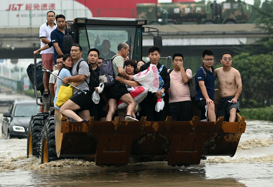 caption: People ride in the front of a wheel loader to cross a flooded street following heavy rains which caused flooding and claimed the lives of at least 63 people in the city of Zhengzhou in China's Henan province on July 23.