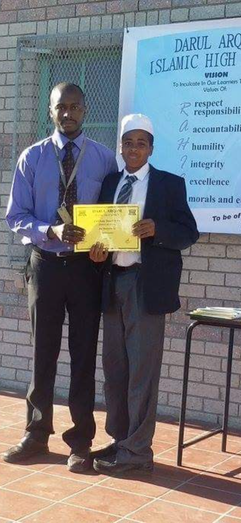 caption: Ahmed Ahmed (right) poses with his father at his 8th grade award ceremony in 2015 in Darul Arqam Islamic High School  in Cape Town, South Africa.