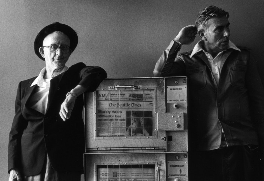 caption: Men with newspaper box, 1981