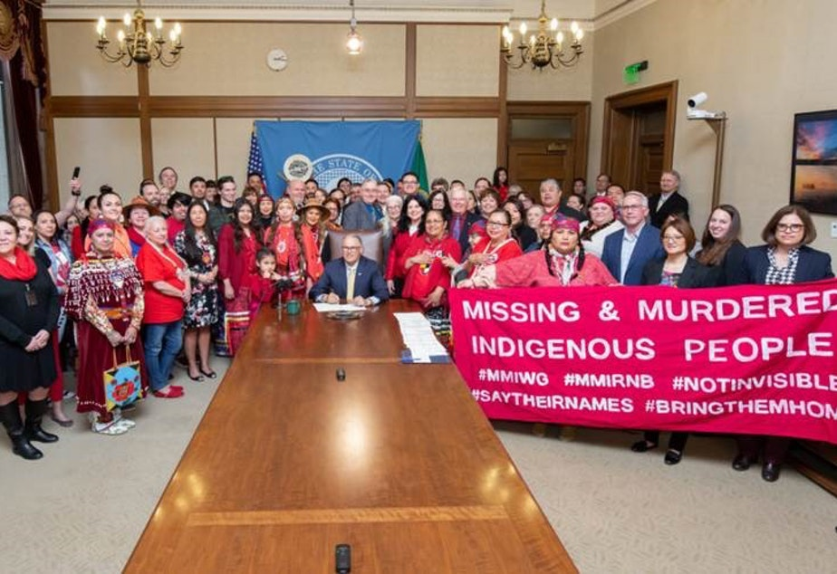caption: Tribal representatives and lawmakers from across the state filled the governor's conference room as Governor Jay Inslee signed HB 1713 on April 24, 2019. Earth-Feather Sovereign and her daughter stand to Inslee's left.