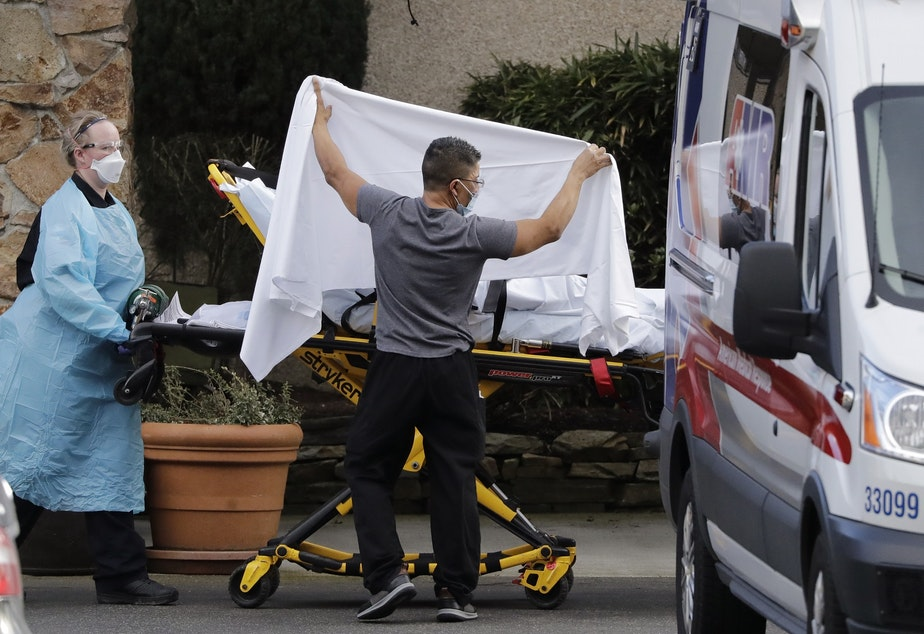 caption: A staff member blocks the view as a person is taken by a stretcher to a waiting ambulance from a nursing facility where more than 50 people are sick and being tested for the COVID-19 virus, Saturday, Feb. 29, 2020, in Kirkland, Wash.