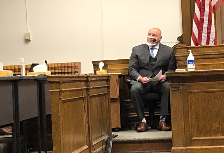 caption: Sgt. Scott Rankin of the Kent Police Department wears a clear face mask to testify in King County Superior Court.