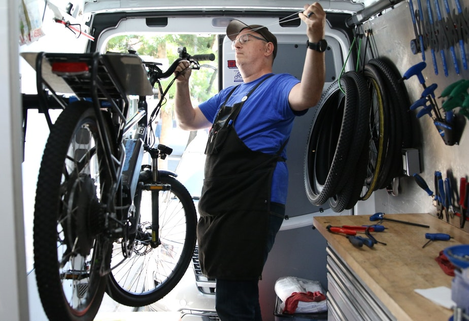 Mike Jenness repairs the ebikes used by Domino's in his van. His bike maintenance business, called Shots and Sprockets, has been growing with the rise of corporate ebike fleets.