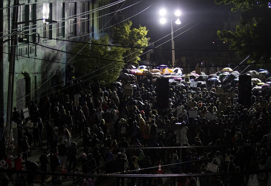 caption: Hundreds of protesters are shown standing arm to arm before a fortified line of police officers in riot gear at 10:54 p.m. on Sunday, June 7, 2020, in Seattle.