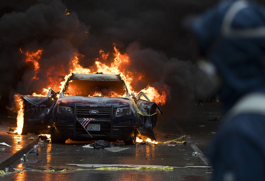 caption: A protester wearing a respirator watches as a small American flag hangs from the grill of a burning Seattle Police Department cruiser as thousands gathered in protest following the murder of George Floyd on Saturday, May 30, 2020, near the intersection of 5th Avenue and Pine Street in Seattle.