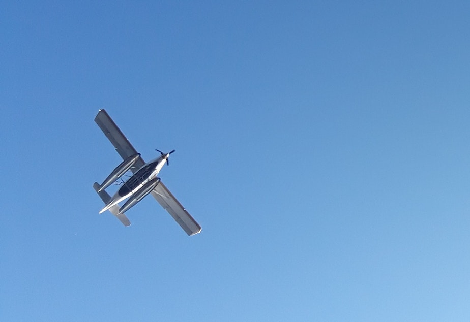 caption: A seaplane, as seen from below, taking off from Lake Union, August 18, 2018.
