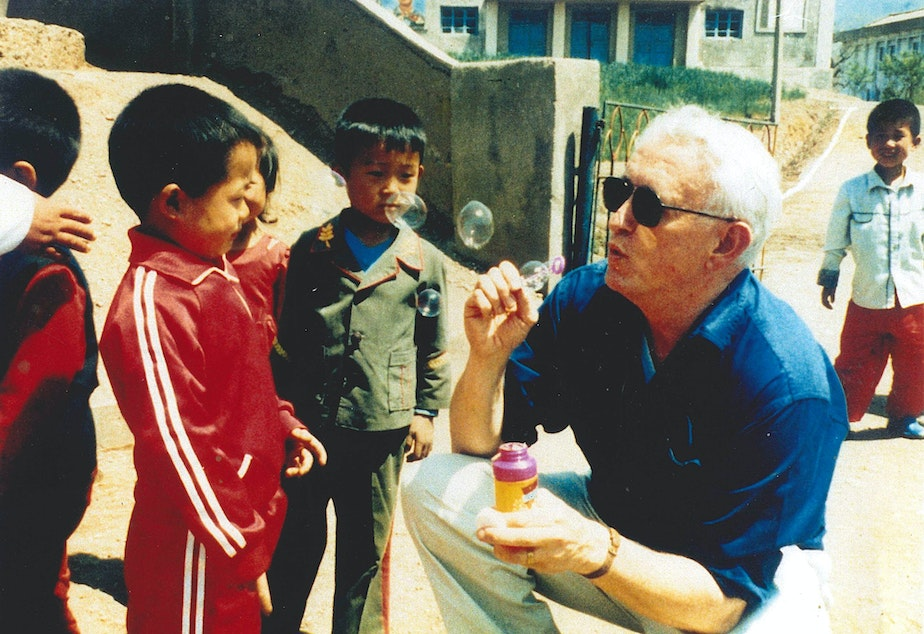 Ralph Munro, Washington's former secretary of state, blows bubbles with Vietnamese refugees. Gov. Dan Evans asked Munro to find out more about the refugees, so he went to Camp Pendleton in California in 1975.