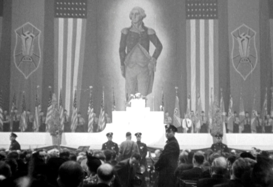 caption: An enormous portrait of George Washington hung alongside swastika banners and American flags at Madison Square Garden.