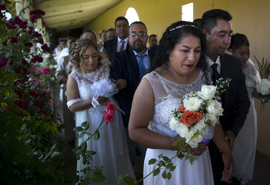 caption: Alma Mejia walks with her soon-to-be husband, Fortino Mejia, along with 22 other couples, to a mass wedding ceremony on Sunday, June 2, 2019, at Our Lady of the Desert Church in Mattawa.