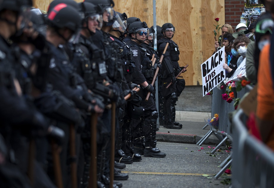 caption: Seattle police officers dressed in riot gear, left, stand in a line across 11th Street, opposite thousands of people protesting police brutality and the unjust deaths of Black Americans at the hands of law enforcement on the fifth day of protests following the violent police killing of George Floyd on Tuesday, June 2, 2020, in the Capitol Hill neighborhood of Seattle.