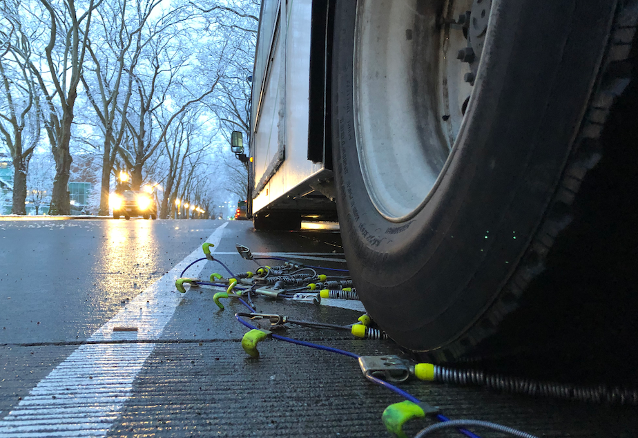 caption: Buses get prepared with tire chains on the University of Washington campus as snow falls on Seattle, Jan. 13, 2020.