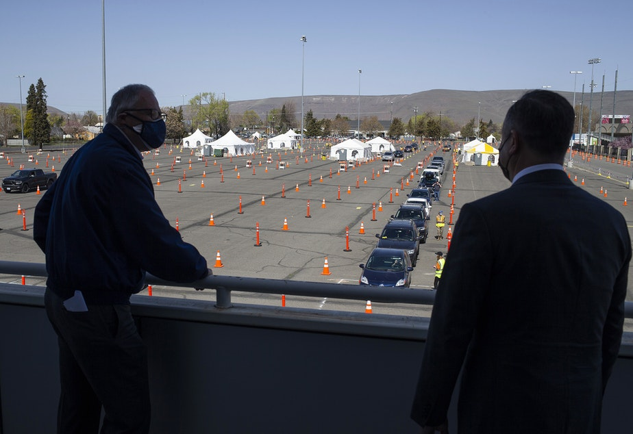 caption: Second Gentleman Douglas Emhoff, right, and Governor Jay Inslee, left, look out over the mass vaccination site at State Fair Park during the coronavirus pandemic Tuesday, April 6, 2021 in Yakima, Wash.