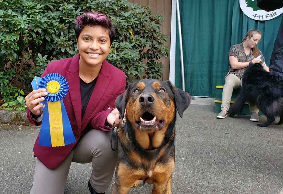 "caption: Jordan Dove and Koda show off their award of merit just moments after presenting to the judges. Jordan's mom calls Koda the ""Michael Jordan of dogs."""