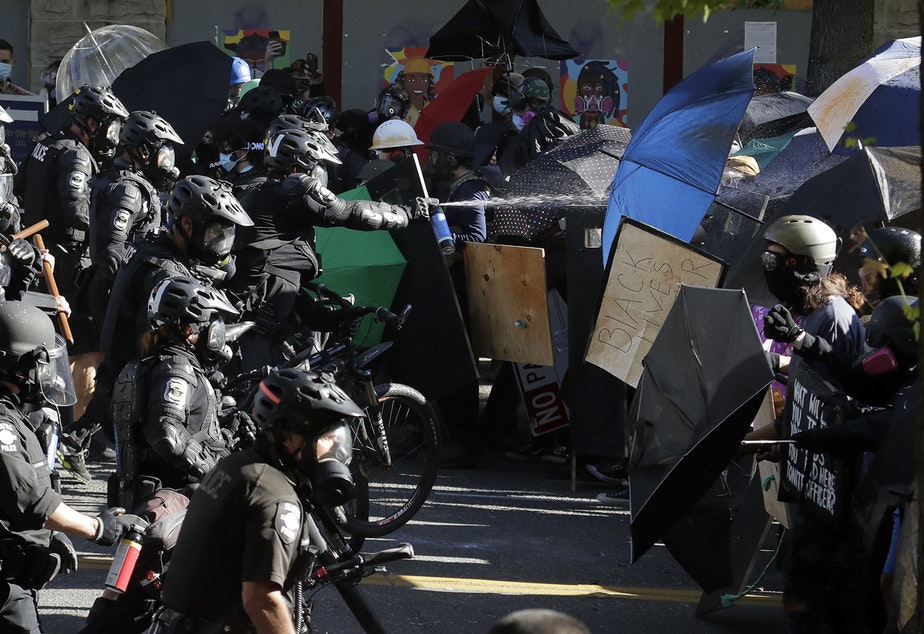 caption: Police pepper spray protesters, Saturday, July 25, 2020, near Seattle Central Community College in Seattle. A large group of protesters were marching Saturday in Seattle in support of Black Lives Matter and against police brutality and racial injustice.