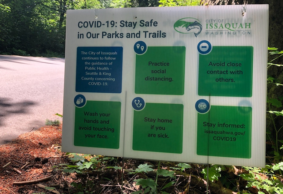 caption: A sign near trails at Tiger Mountain outside of Issaquah, urging awareness of Covid-19 while in nature.