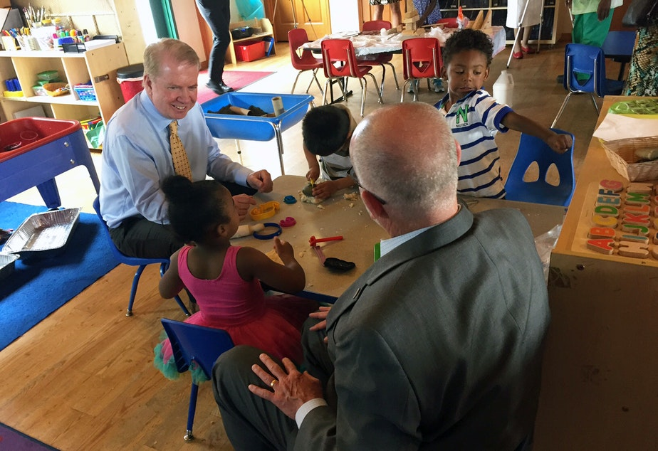 caption: Seattle Mayor Ed Murray and City Councilmember Tim Burgess chat over playdough with preschoolers in July 2015 at Causey's Learning Center, one of the first Seattle Preschool Program providers.